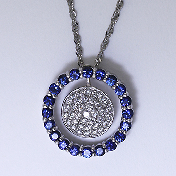 Sparkling bead set diamonds surrounded by a ring of sapphires make a beautiful pendant.