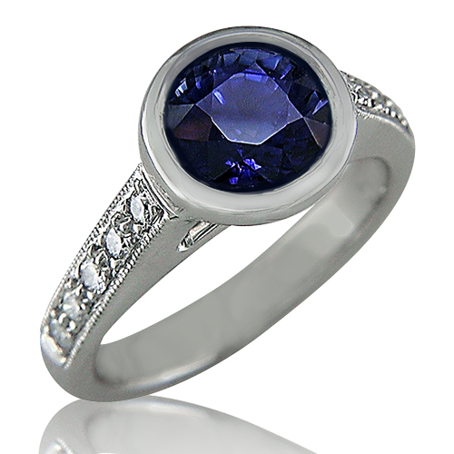 Style:LRR70 ~ A round blue sapphire bezel set with side bead set diamonds.